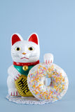 Maneki neko donut. A maneki neko presenting a multicolor donuts on a doily paper and a pop colorful background. Minimal quirky color still life photography stock photo
