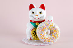 Maneki neko donut. A maneki neko presenting a multicolor donuts on a doily paper and a pop colorful background. Minimal quirky color still life photography stock photos
