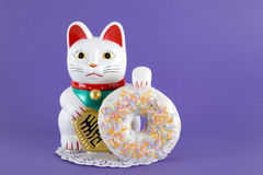 Maneki neko donut. A maneki neko presenting a multicolor donuts on a doily paper and a pop colorful background. Minimal quirky color still life photography royalty free stock images