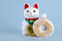 Maneki neko donut. A maneki neko presenting a multicolor donuts on a doily paper and a pop colorful background. Minimal quirky color still life photography royalty free stock photo
