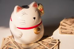 Maneki-neko, Japanese lucky cat with Yen bank note. Concept rich and save money royalty free stock photography