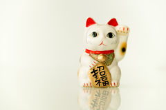 Maneki Neko - Luckly Cat. Japanese beckoning cat (Maneki Neko) also means bring wealth to you while a right paw raised, currency sign for you to replace stock image