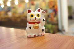 Maneki-neko is lucky cat. The maneki-neko is a Japanese figuring which is often believed to bring good luck to the owner. It looks like a cat stock photo