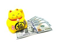 Maneki Neko, montrant Lucky Yellow Cat et des billets d'un dollar du doigt Photo stock