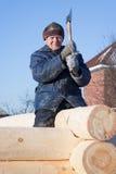 Manen bygger ett trähus royaltyfria foton