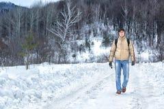 Manen går längs en snöig väg Arkivbilder