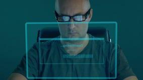Manen hacker i t-skjorta sitter och skriver koden för lösenorddecryption En hacker får tillträde till data och nedladdar dess til lager videofilmer