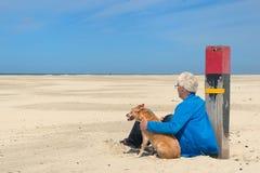 Manen med förföljer på stranden Arkivbild