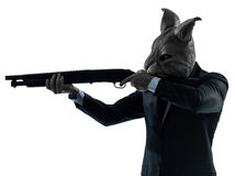 Manen med kanin maskerar jakt med hagelgevärsilhouetteståenden Arkivfoto