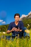 Manen med ringer sammanträde i bergen Fotografering för Bildbyråer