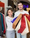 Manen och kvinnan med shopping hänger lös Arkivfoton