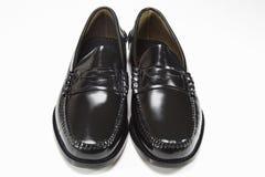 Manen parar av svart skor på vit Royaltyfri Bild