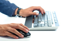 Manen räcker arbetet med datormusen, och datoren skrivar Arkivbild