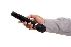 Manen räcker den hållande mikrofonen Arkivfoto