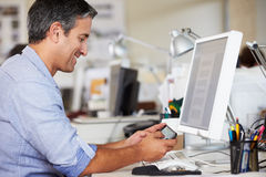 Manen som använder mobil, ringer på skrivbordet i upptaget idérikt kontor Royaltyfri Bild