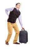 Manen som lyfter hans bagage och lider från en baksida, smärtar Royaltyfri Foto