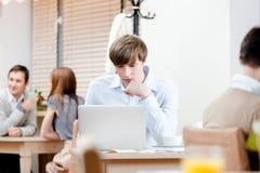 Manen surfar på internet på bärbar dator Fotografering för Bildbyråer