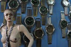 Manequim danificado de uma mulher ao lado dos grandes relógios em uma parede azul fotos de stock