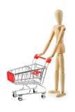 Manequim de madeira com o carrinho de compras no fundo branco Fotografia de Stock Royalty Free