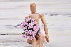 Manequim de madeira que guarda flores Imagem de Stock Royalty Free