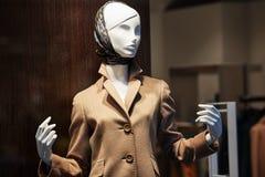 Manequim que está na exposição da janela de loja da loja da roupa ocasional das mulheres fotografia de stock royalty free