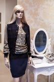 Manequim que está na exposição da janela de loja da loja da roupa ocasional das mulheres imagem de stock
