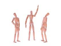 Manequins de madeira um que mostram e dois que olham acima Isolado no branco imagem de stock royalty free