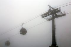Manera de cable con el fondo profundo del blanco de la niebla de dos coches de cabina Imagenes de archivo