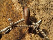 Manera de los escaladores Planche la cuerda torcida fijada en bloque por los ganchos rápidos de los tornillos El extremo de la cu Imágenes de archivo libres de regalías