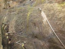 Manera de los escaladores Planche la cuerda torcida fijada en bloque por los ganchos rápidos de los tornillos El extremo de la cu Imagen de archivo