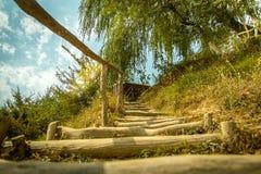 Manera de madera de la escalera en hierba a la colina Foto de archivo