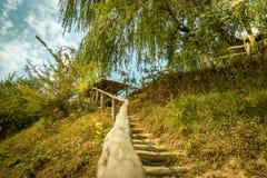 Manera de madera de la escalera en hierba a la colina Imagen de archivo