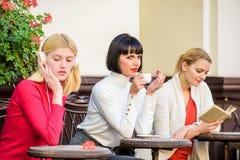 Manera de relajarse y de recargar Ocio femenino Terraza bonita de las mujeres del grupo entretenerse con la lectura y escuchar imágenes de archivo libres de regalías