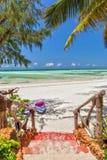 Manera a la playa tropical de la arena blanca con los barcos debajo de la palmera Imágenes de archivo libres de regalías