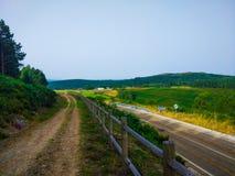 Manera rural además del camino en un prado de la hierba verde con la montaña imagen de archivo libre de regalías