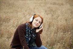 Manera sonriente joven con los auriculares en el campo. Fotografía de archivo libre de regalías