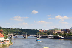Manes Bridge, boats on river Vltava and Czech Philharmonic in Prague Stock Photo