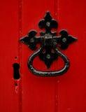 Maneta en una puerta roja Imagenes de archivo