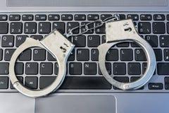 Manette che si trovano su una tastiera di computer che simbolizza crimine cyber fotografia stock