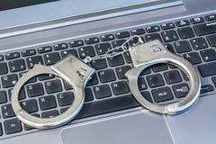 Manette che si trovano sulla tastiera di computer come simbolo per il crimine cyber fotografia stock libera da diritti