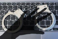 Manette che si trovano sulla tastiera di computer più ombra scura di una mano che simbolizza crimine cyber immagine stock