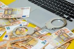 Manette con soldi sulla tastiera del computer portatile fotografia stock libera da diritti