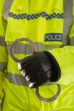 Manette della holding dell'ufficiale di polizia Fotografie Stock Libere da Diritti