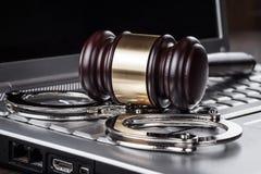 Manette e martelletto del giudice sul concetto del computer Fotografie Stock