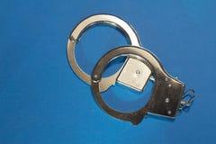 Manette su fondo blu Fotografia Stock Libera da Diritti