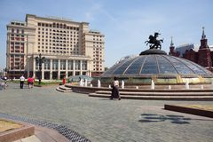 Manezh Square, glass dome, Four Seasons Hotel Moscow and walking people Royalty Free Stock Photo
