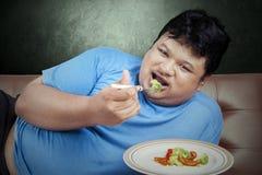Manförsök att banta, genom att äta grönsaken arkivfoton