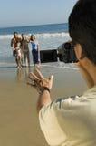 Manfilmandefamilj på stranden Royaltyfria Bilder