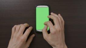 Manfingrar som gör gester som trycker på och nallar den gröna skärmen av socialt massmedia för smartphonen, knyter kontakt böjels lager videofilmer