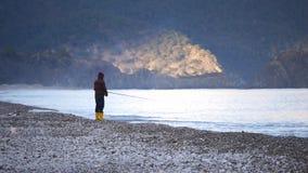 Manfiske på stranden i solnedgång arkivfilmer